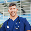 smiling-male-healthcare-worker-outside-hospital-resized
